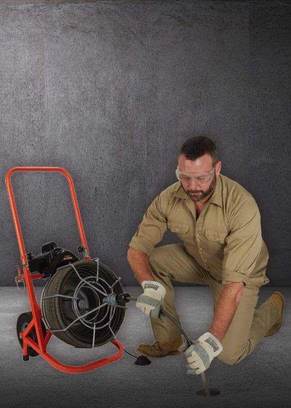 Plumber Performing Rooting Services on Cement Floor